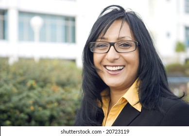 A beautiful indian business woman wearing spectacles gives a stunning smile as she stands in front of office buildings