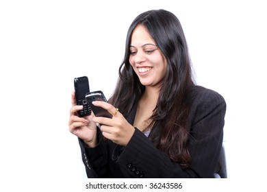 A beautiful Indian businesswoman choosing in two cellphones, on white background.