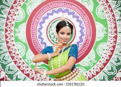 Beautiful Indian classical odissi dancer posing infront of wall Street Art (Pattachitra) at Bhubaneswar, Odisha, India -Close up