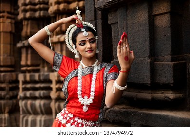 Beautiful Indian classical Odissi dancer looks at the mirror posing in front of Mukteshvara Temple,Bhubaneswar, Odisha, India