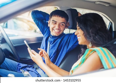 Beautiful indian couple in a car using mobile phone to plan their journey online