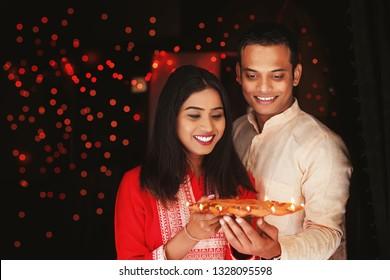 Beautiful Indian couple holding diya thali for Diwali celebration