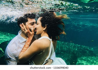 Beautiful Indian couple kisses under the water