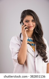 Beautiful Indian female doctor speaking or presenting smartphone or Tablet computer. Standing isolated over grey background