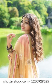 Beautiful indian girl in saree standing near lake in summer time.