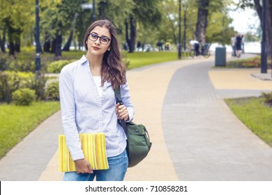 Beautiful Indian girl, student, with books near college. Female mixed race stands at the campus.