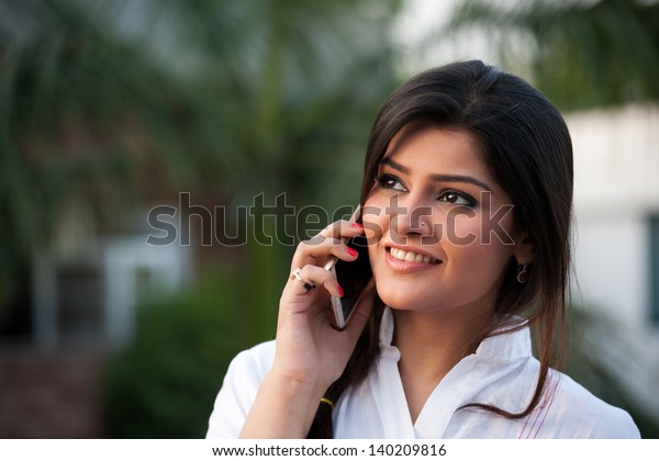beautiful Indian girl talking over the phone in outdoor.