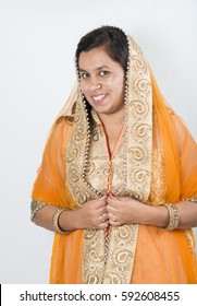 Beautiful Indian girl in traditional Indian clothing, posing isolated over white background.