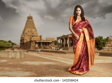 Beautiful Indian girl in traditional Indian sari on temple background.