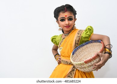 Beautiful Indian  girl or women or kid wearing sari or saree traditional dress for females in India Rajasthan. Dressed up as Indian folk/classical dancer holding basket. wearing ornaments and makeup.