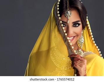 Beautiful indian girl . Young hindu woman model  with tatoo mehndi  and kundan jewelry . Traditional Indian costume yellow saree . Indian or Muslim woman covers her face.