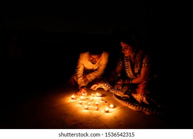 Beautiful Indian Gujarati couple in Indian traditional dress lightening Diwali diya/lamps sitting on the floor in darkness on Diwali evening. Indian lifestyle and Diwali celebration