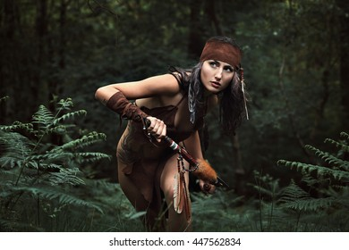 Beautiful indian huntress in a green forest . Native warrior