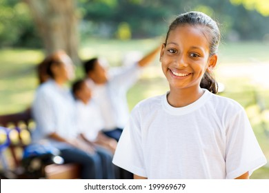 beautiful indian little girl standing in front of family outdoors