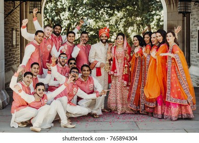 Beautiful Indian newlyweds stands with their bridesmaids and groomsmen dressed in saris, sherwanis, lehengas outside and look cheerful