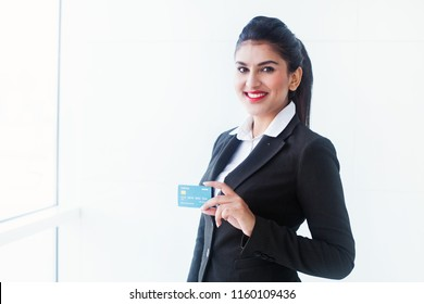 Beautiful indian woman in formals holding credit card