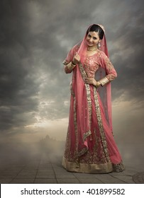 Beautiful Indian woman in glamorous outfit and jewelry with makeup in outdoor background.