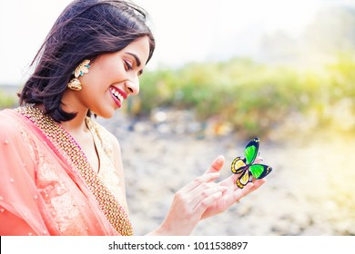 Beautiful indian woman holding butterfly in her hand