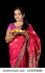 A beautiful Indian Indian woman holding a hindu ritual plate, on black studio background.