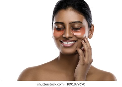 Beautiful Indian woman with hydrating eye patches under her eyes on white background.