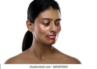 Beautiful Indian woman with hydrating eye patches and lip mask on her face against white background.