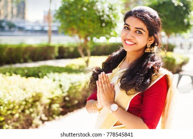 Beautiful indian woman from Kerala wearing traditional clothes showing namaste gesture