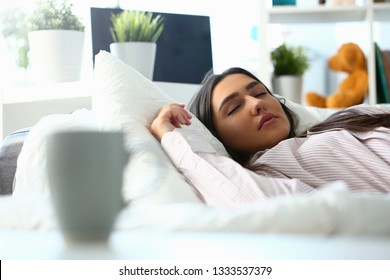 Beautiful indian woman peacefully lying in bed sleeping early morning while alarm clock going to ring awakening. Early wake up, not getting enough sleep, oversleep, getting work time concept