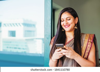 Beautiful Indian woman in a saree using her mobile phone and smiling standing on a balcony with city reflected in the window