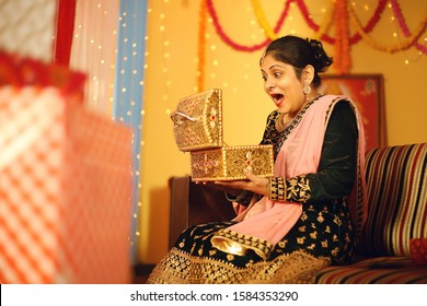Beautiful Indian woman sitting in traditional dress. Holding jewelry box in hand. Isolated on decorative background.