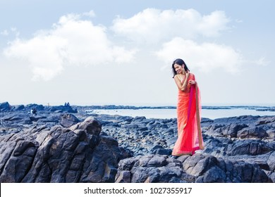 Beautiful indian woman standing on a beach wearing saree