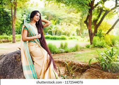 Beautiful indian woman with very long hair wearing saree in a park