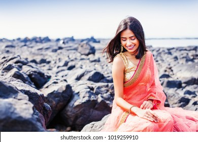 Beautiful indian woman wearing saree sitting on a shore in Mumbai
