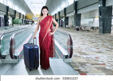 Beautiful indian woman wearing traditional clothes and standing in the airport hall while carrying suitcase
