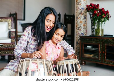 Beautiful Indian woman wearing traditional kurta teaching her daughter to play Tabla