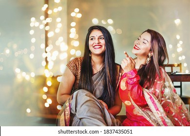 Beautiful Indian women in festive outfit posing as best friends, laughing over a nice bokeh background