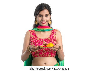 Beautiful Indian young girl holding pooja thali or performing worship on a white background