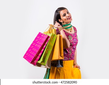 Beautiful Indian young girl holding many shopping bags while wearing traditional ethnic wear. Isolated over white background