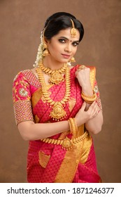 Beautiful Indian young Hindu Bride against brown background in studio shot