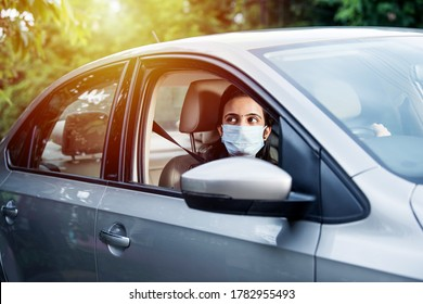 Beautiful Indian young woman in a mask sitting in a car, protective mask against coronavirus, driver on a city street during covid-19 pandemic