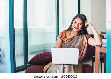 Beautiful Indian young woman in a saree using her laptop, working from home