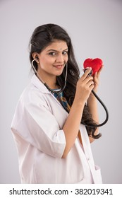 Beautiful Indian/Asian female Doctor holding red stuffed heart toy as a heart care concept. standing isolated over white background