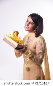 Beautiful Indian/Asian girl in traditional wear opening her gift while looking at camera, isolated over white background