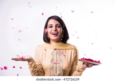 Beautiful Indian/Asian young girl in traditional wear throwing rose petals from plate, standing isolated over white background
