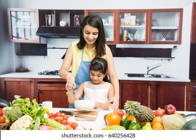 Beautiful Indian/Asian young Mother and Daughter in kitchen, with table full of fruits and vegetables