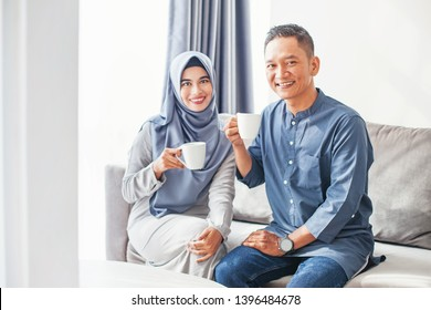 Beautiful indonesian muslim couple drinking coffee at home