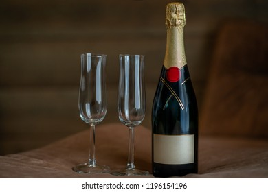 Beautiful indoor view of a champagne bottle with two glasses on a suede table with dark background.