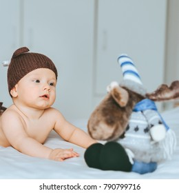 beautiful infant child in knitted brown hat with toy moose in bed