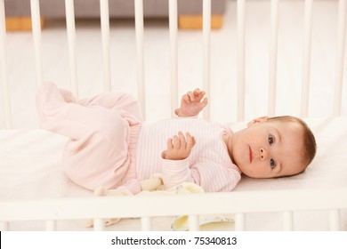 Beautiful infant girl in cute pink dress lying in crib.?