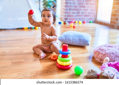 Beautiful infant happy at kindergarten around colorful toys