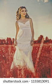 Beautiful infrared blonde. Summertime female portrait. Young adult woman walking on the meadow